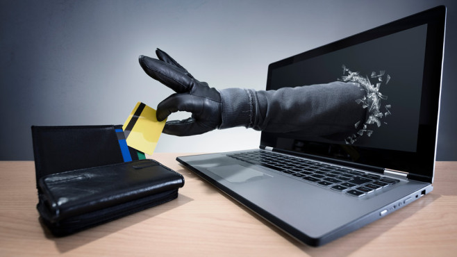 Hand greift aus Computer nach Kreditkarte ©©istock.com/BrianAJackson