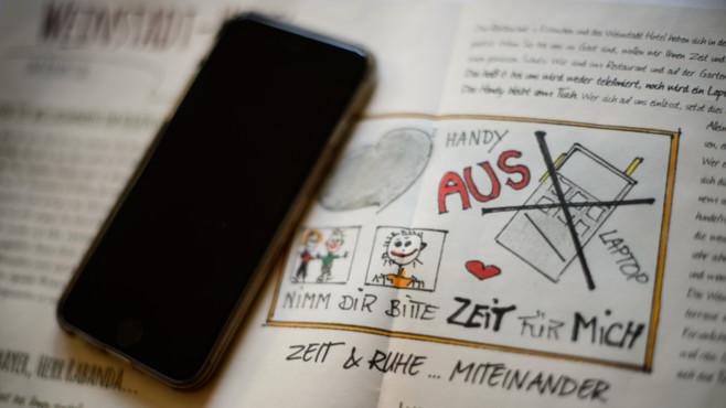 Handy liegt auf Hotelbroschüre ©Sina Schuldt/dpa