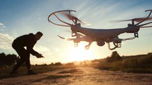Mann steuert Drohne im Sonnenuntergang ©©istock.com/golubovy