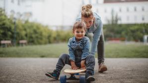 Frau schiebt Jungen auf Skateboard an ©©istock.com/AleksandarNakic