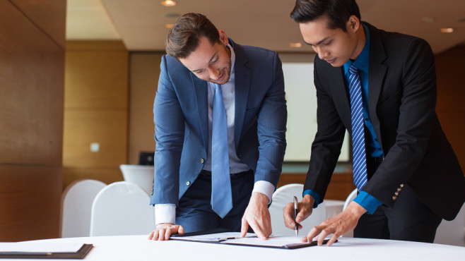 Zwei stehende Männer unterschreiben Vertrag ©©istock.com/MangoStar_Studio