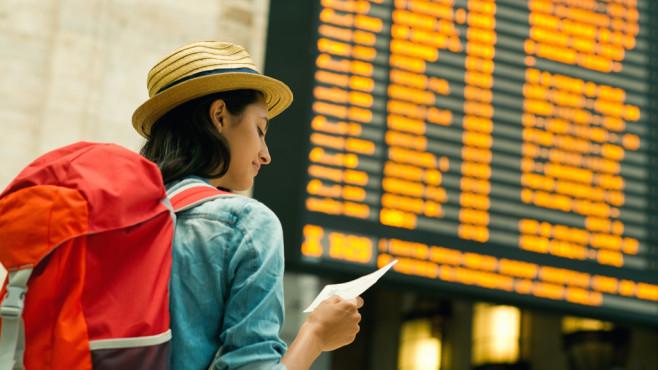Junge Frau mit Rucksack vor Abflugtafel ©©istock.com/MStudioImages