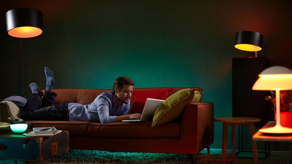 Mann liegt auf einer Couch und liest.