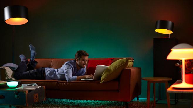 Mann liegt auf einer Couch und liest.©Philips