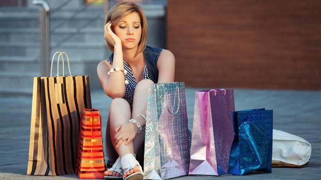 Eine junge Frau sitzt unglücklich zwischen Einkaufstaschen©iStock.com/a-wrangler