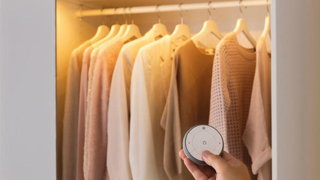 Eine Hand steuert Lampen im beleuchteten Kleiderschrank per Fernbedienung. ©IKEA