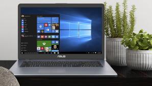 Das Asus Vivobook 17 auf einem Schreibtisch neben Pflanzen.©ASUS, iStock.com/ExperienceInteriors