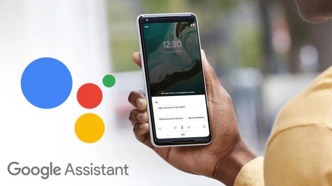 Hand hält ein Smartphone, links daneben das Google-Assistant-Logo©Google