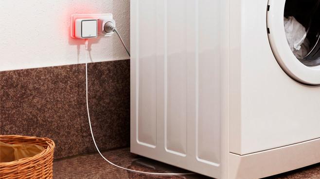 Eve Water Guard steckt in der Steckdose neben einer Waschmaschine und leuctet rot©Eve
