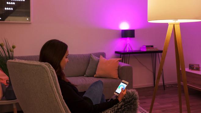 Tint-Lampe und Smartphone-Nutzerin im Wohnzimmer©Müller-Licht