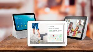 Drei Smart Displays stehen auf einem Tisch vor verschwommenem Hintergrund.©iStock.com/Weedezign, Amazon, Google, Lenovo