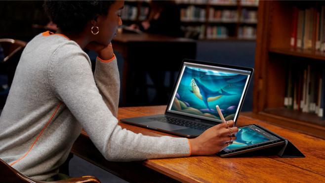 Frau benutzt iPad als zweites Display für den Mac.©Apple