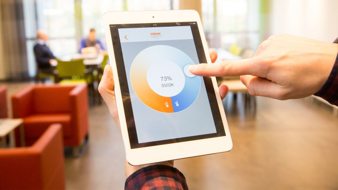 Hand tippt zeigt aufs iPad mit der Lightify-App©Osram