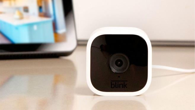 Die Blink Mini liegt auf dem Tisch vor einem Echo Show©Amazon