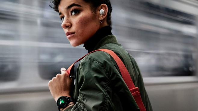 Frau mit Galaxy Buds in den Ohren steht am Bahnhof©Samsung
