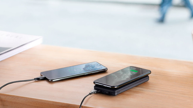 Anker PowerCore Wireless 10K lädt ein Smartphone per Kabel auf dem Tisch.©Anker