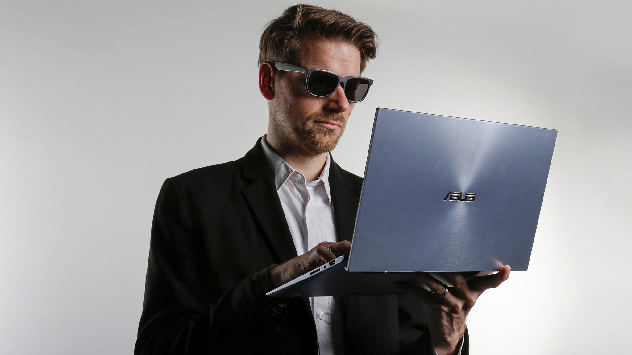 Redakteur mit Sonnenbrille und Jacket hält das Asus ZenBook 14 und schaut auf das Display.©COMPUTER BILD