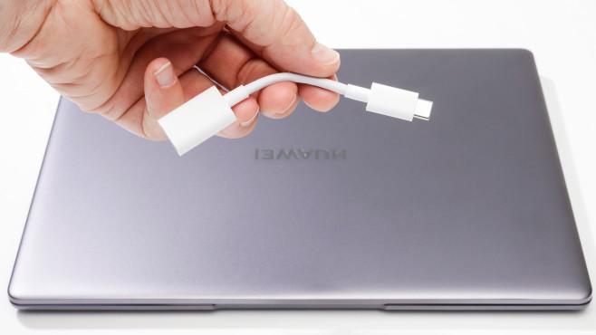 Hand hält USB-Adapter über das Huawei MateBook (2020)©COMPUTER BILD