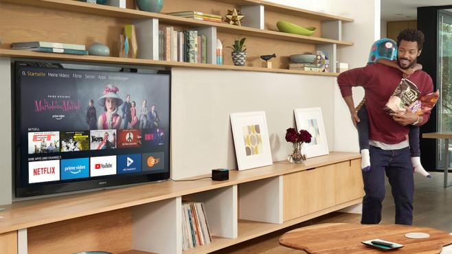 Vater und Kind schauen im Wohnzimmer auf den Fernseher©Amazon