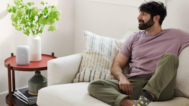Mann hört auf der Couch Musik über den Nest Audio.©Google