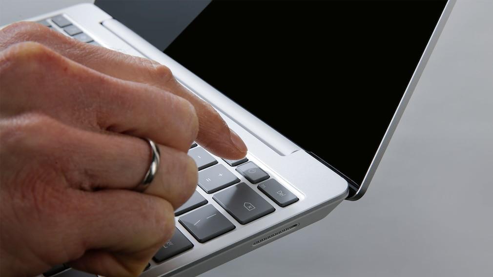 Finger zeigt auf den Fingerabdrucksensor des Microsoft Surface Laptop Go.