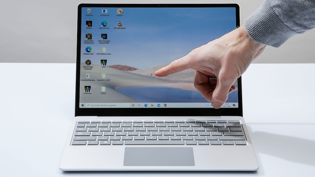 Hand berührt den Touchscreen des Microsoft Surface Laptop Go.