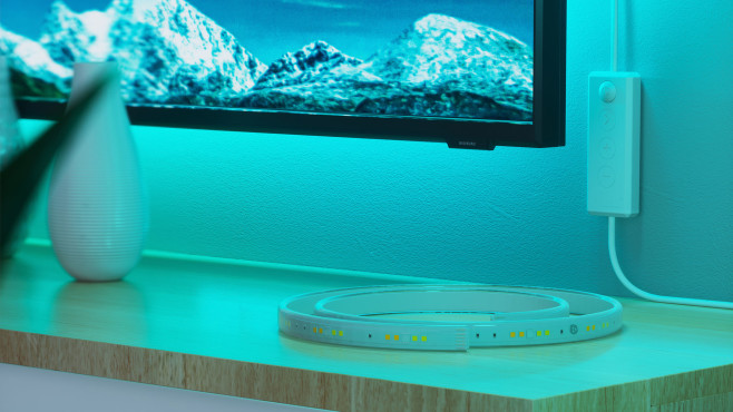 Der Nanoleaf Lightstrip liegt auf einem TV-Schrank, die Fernbedienung hängt ander Wand.©Nanoleaf