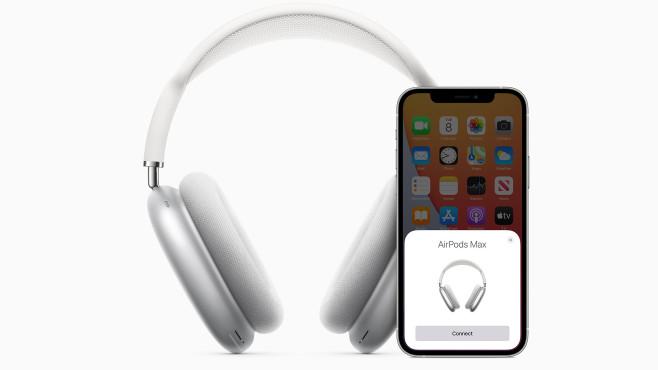 Apple AirPods Max neben einem iPhone vor weißem Hintergrund.©Apple