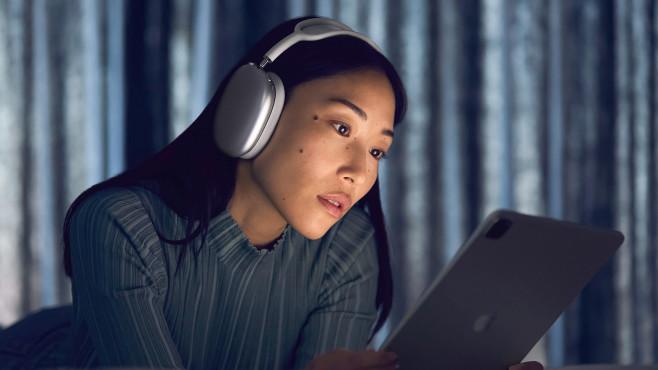 Frau trägt die AirPods Max und schaut auf ein iPad.©Apple