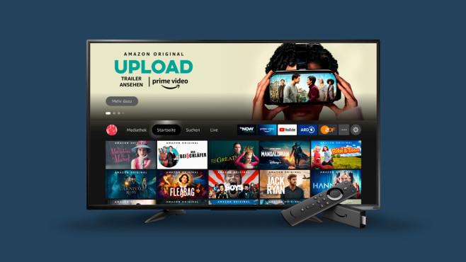 Die neue Fire-TV-Oberfläche auf einem Fernseher, davor liegt ein Fire TV Stick mit Fernbedienung.©Amazon