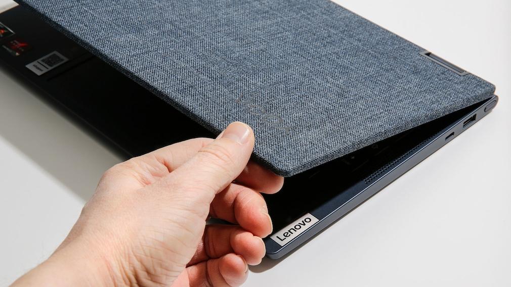 Hand berührt die Stoffrückseite des Lenovo Yoga 6.