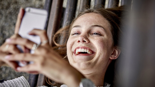 Smartphone-Nutzerin lacht©gettyimages.de / Oliver Rossi