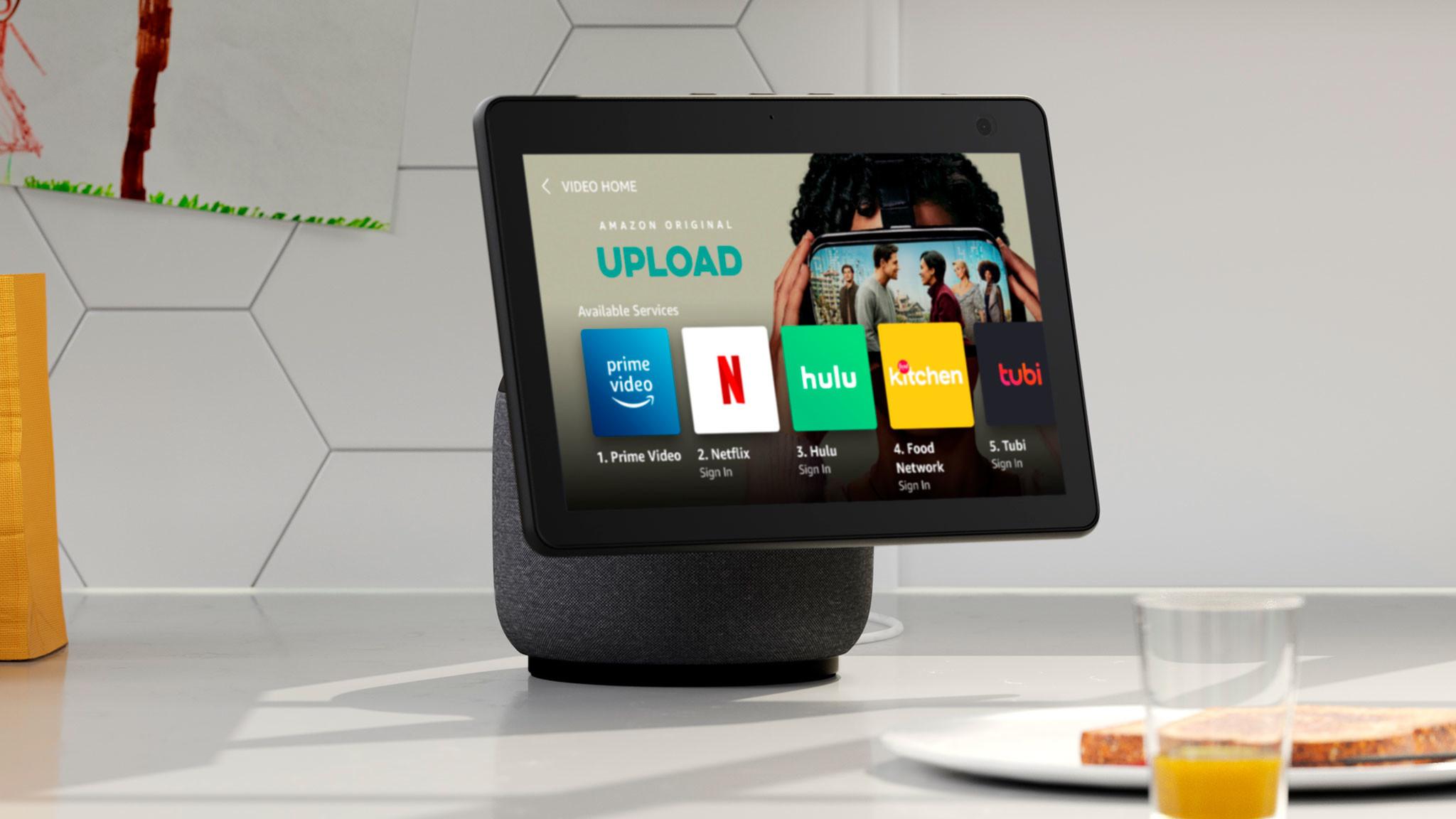 Der Amazon Echo Show 10 steht in einer Küche vor einem Teller mit Schinken und einem Glas Saft.©Amazon