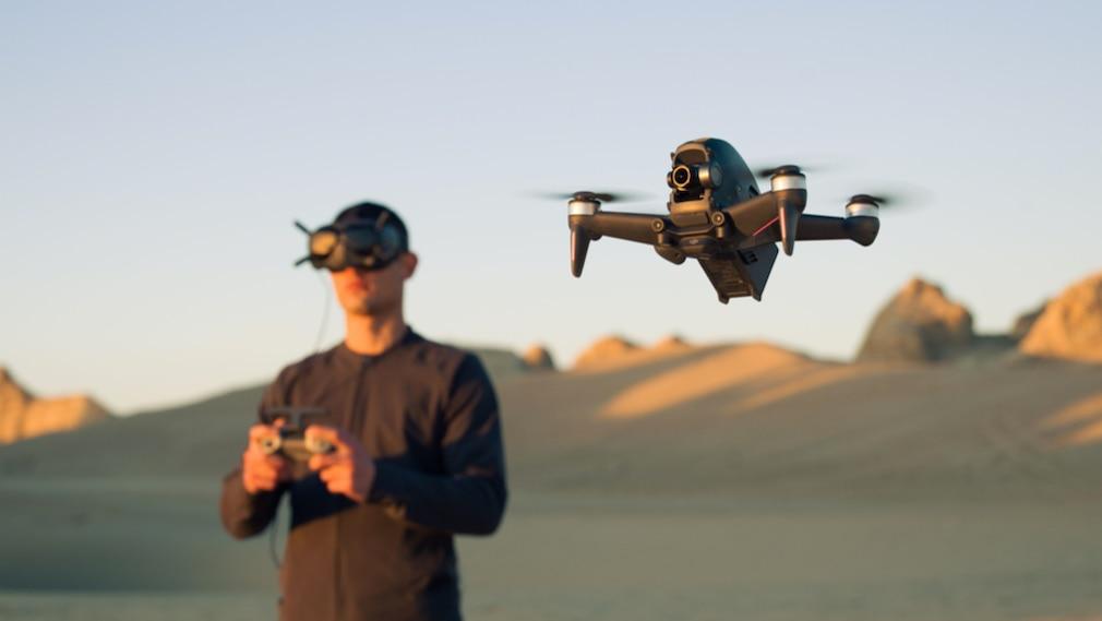 DJI FPV-Drohne und Pilot mit Googles-Brille im HIntergund©DJI