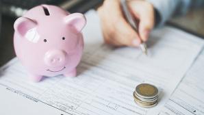 Rosa Sparschwein steht auf Vertrag, der gerade unterschrieben wird©iStock.com/Enes Evren