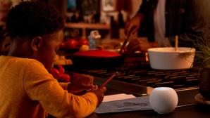 HomePod mini steht auf einem Tisch, daneben macht ein Kind Schulaufgaben.©Apple