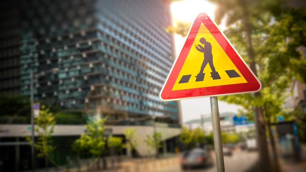 Zebrastreifen-Schild mit einer Person, die auf ihr Handy schaut.