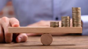 Drei Stapel Münzen auf einer Holzwippe©iStock.com/ AndreyPopov