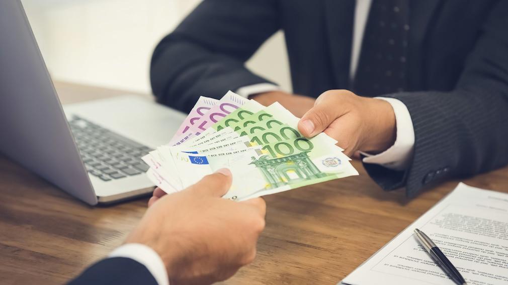 Ausschnitt Männerhand übergibt 100 Euro-Scheine an eine andere Männerhand
