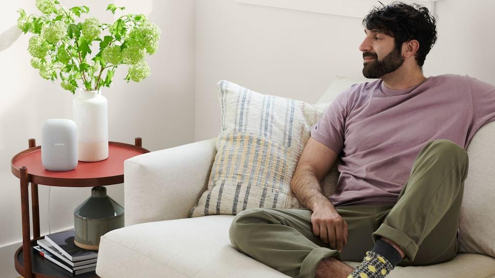 Mann hört auf der Couch Musik über den Nest Audio.