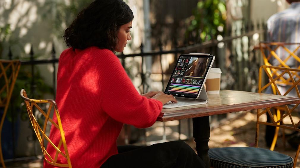 Frau arbeitet draußen mit dem iPad Pro.
