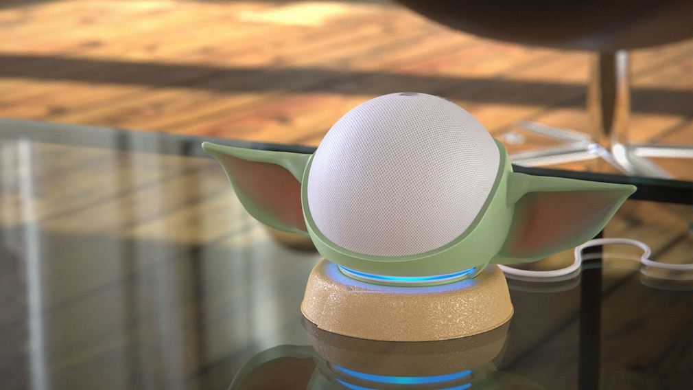 Otterbox-Ständer in Form von Baby Yoda und Amazon Echo Dot stehen auf einem Glastisch.