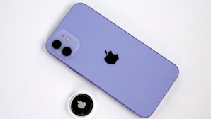iPhone 12 liegt neben einem AirTag auf dem Tisch.©COMPUTER BILD