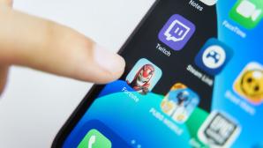 Ein Zeigefinger tippt auf die Fortnite-App auf dem iPhone.©iStock.com/ Savusia Konstantin