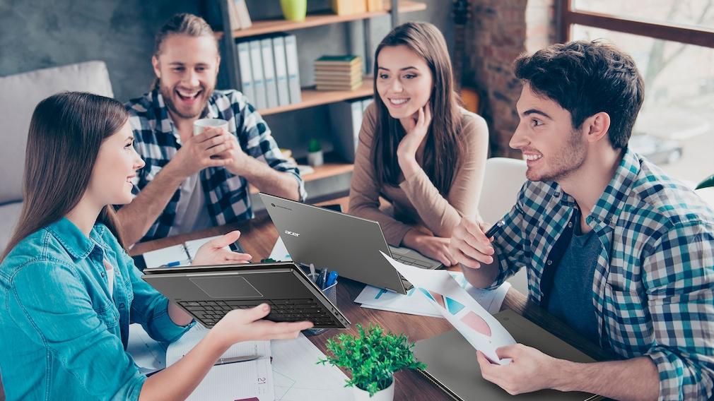 Eine Gruppe Studenten sitzt mit Chromebooks an einem Tisch.