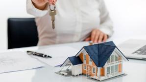 Hausmodell auf Tisch und Person hält Schlüssel darüber©iStock.com/guvendemir