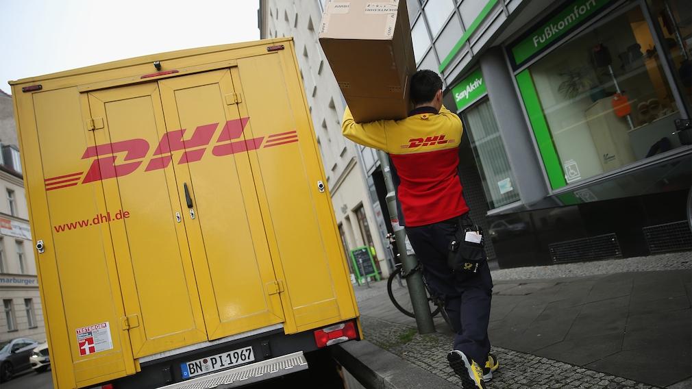 DHL-Bote trägt ein Paket neben dem Zustellfahrzeug