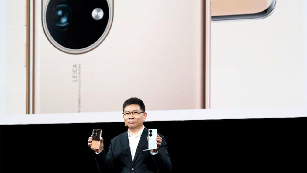 Mann hält Smartphones in die Kamera.