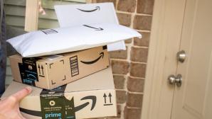 Hand hält viele Amazon-Pakete.©iStock.com/ Daria Nipot