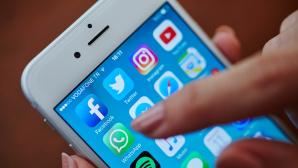 Finger zeigt auf das WhatsApp-Symbol auf einem iPhone.©iStock.com/bombuscreative